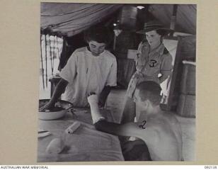 awm-092135-matron-major-janet-cook-at-moratai-observing-a-patient-injured-at-tarakan